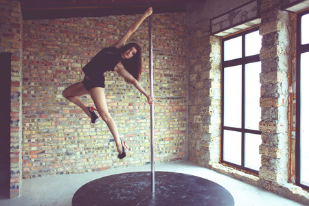 Young pole dancer woman trains on grunge interior with brick walls photo
