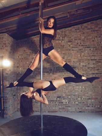 Two young pole dancers train in duet on grunge interior with brick walls