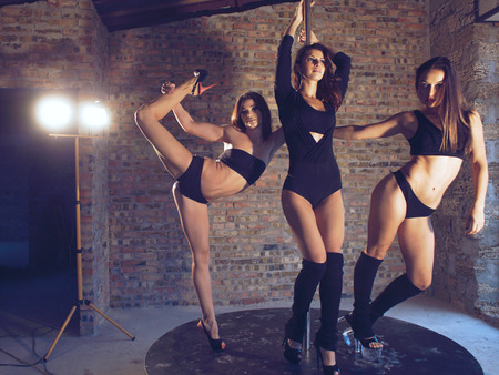 Three young pole dancers posing on a stage on grunge interior with brick walls
