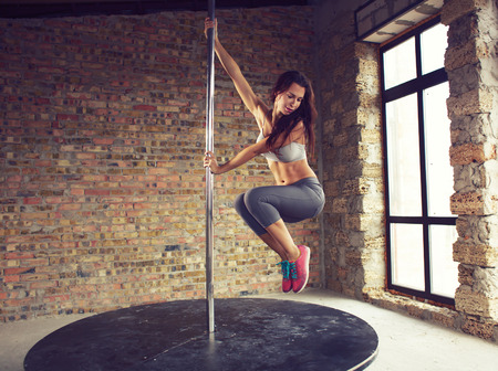 Young pole dancer woman wearing grey sports wear and colorful sneakers trains on grunge interior with brick walls photo
