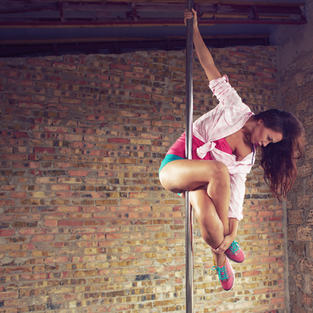 Young pole dancer woman wearing colorful sports wear trains on grunge interior with brick walls, right align, square composition photo
