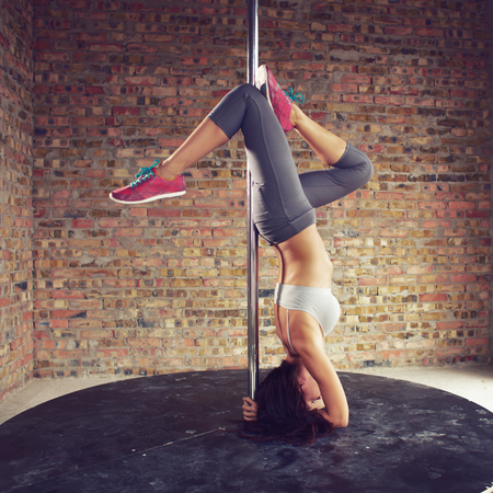 pole dance: Young pole dancer woman wearing grey sports wear and colorful sneakers trains on grunge interior with brick walls, square composition Stock Photo