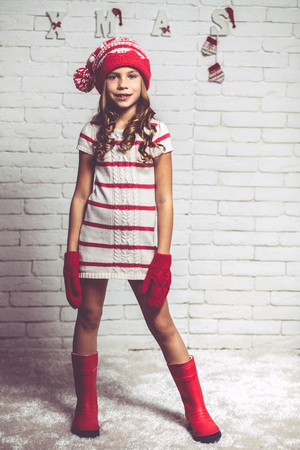 little model: Little fashion girl in fashion Christmas clothes posing over white brick background, full length