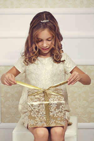 Portrait of luxury little princess with gold gift box Stock Photo