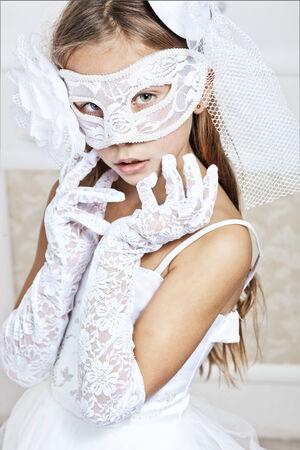 Portrait of a fashion girl wearing wedding dress and venetian mask photo
