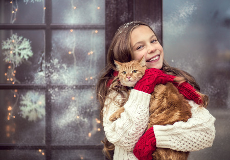 beautiful preteen girl: Child girl hugging her pet staying near her house decorated before Christmas