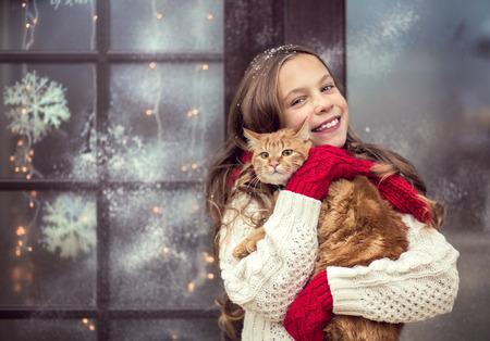 Kind meisje knuffelen haar huisdier verblijft in de buurt van haar huis ingericht voor de kerst Stockfoto