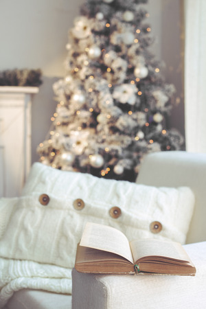 Detail of beautiful holdiay decorated room with Christmas tree and white comfortable chair with soft knitted blanket and cushion on it, reading time