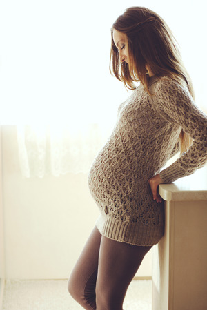 sueteres: Inicio acogedor retrato de mujer embarazada vistiendo suéter de cachemira caliente descansando en su casa