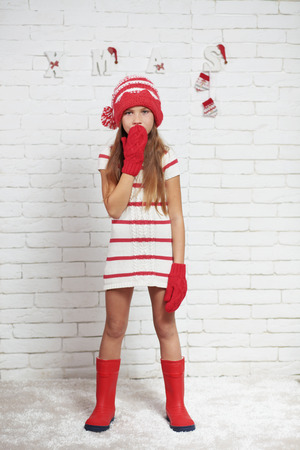 girl boots: Little fashion girl in fashion Christmas clothes posing over white brick background, full length