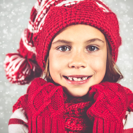 child model: Little fashion girl in fashion Christmas clothes posing over white brick background, full length