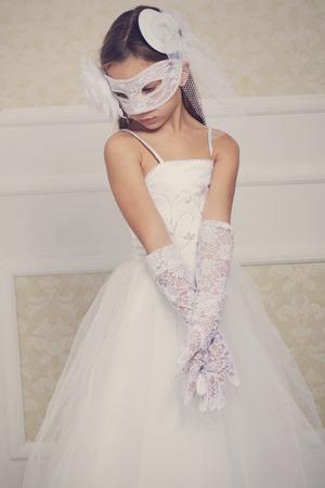 Portrait of a fashion girl wearing wedding dress and venetian mask Stock Photo