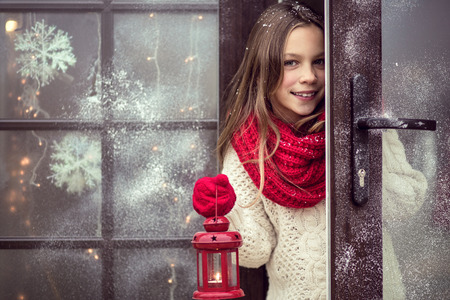 warm welcome: Child girl welcome guests and holding holiday lantern, snow weather, house is decorated before Christmas