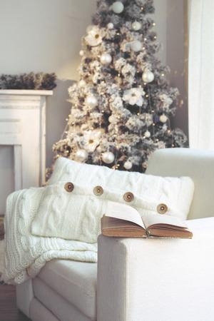 camino natale: Bella holdiay sala decorata con albero di Natale e sedia bianca confortevole morbida coperta di maglia e cuscino su di esso, il tempo di lettura