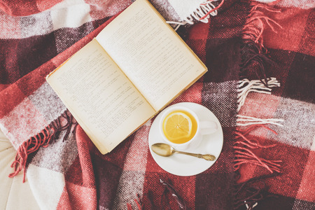 Cup of hot tea and reading on a blanket, instagram style toned. Top view point. Imagens