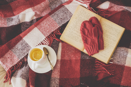 domestic scene: Cup of hot tea and reading on a blanket, instagram style toned. Top view point. Stock Photo