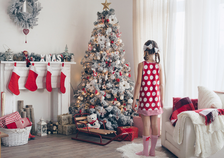 camino natale: Ragazza del bambino in piedi vicino albero di Natale decorato e camino in bella camera d'albergo la mattina di vacanza