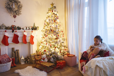 Child girl sitting near decorated Christmas tree and fireplace in comfortable chair at home photo
