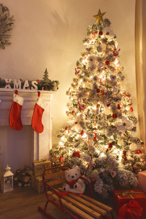 Schöne holdiay eingerichtetes Zimmer mit Weihnachtsbaum mit Geschenken darunter Standard-Bild - 34257565