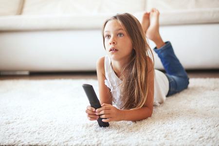 tv: 8 ans enfants regarder la télévision fixant sur un tapis blanc seul à la maison