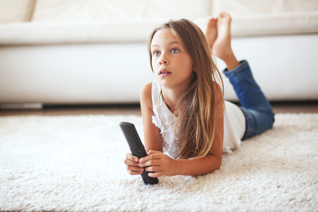 alone: 8 years old child watching tv laying down on a white carpet at home alone