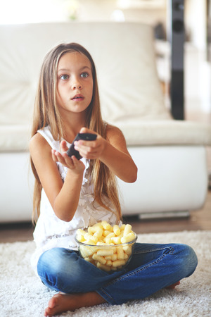8 years old child watching tv sitting on a white carpet at home alone Stock fotó