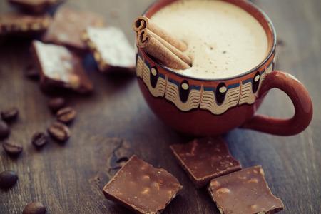 chocolate caliente: Taza de coffe caliente con palitos de canela en el fondo de madera vintage, atención selectiva