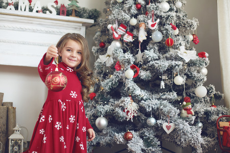 home decorating: 5 years old little girl decorating Christmas tree at home