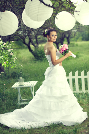 hanging woman: Beautiful bride posing with white decor under paper lanterns in beautiful garden at outdoor wedding ceremony