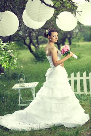ropa colgada: Hermosa novia posando con decoración en blanco debajo de las linternas de papel en el hermoso jardín en la ceremonia de boda al aire libre