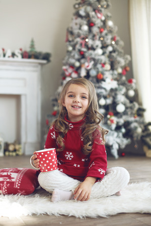 christmas morning: 5 years old little girl drinking milk near Christmas tree in morning at home Stock Photo