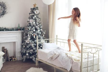 despertarse: Preadolescente estela niño niña y saltando en su cama cerca del árbol de Navidad decorado en la hermosa habitación de hotel en la mañana de fiesta Foto de archivo