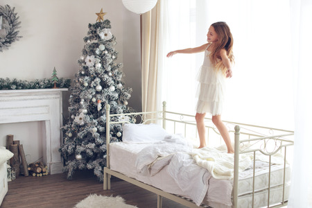 Preteen child girl wake up and jumping on her bed near decorated Christmas tree in beautiful hotel room in the holiday morning Stock Photo