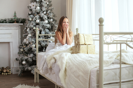 teen girl bedroom: Preteen child girl wake up in her bed near decorated Christmas tree in beautiful hotel room in the holiday morning, surprised with presents Stock Photo