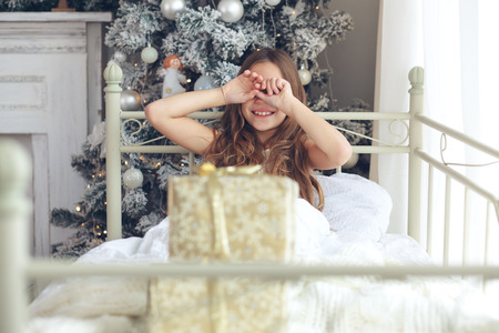 beautiful preteen girl: Preteen child girl wake up in her bed near decorated Christmas tree in beautiful hotel room in the holiday morning, enjoing with presents