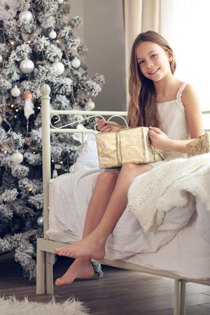 traditional gifts: Preteen child girl wake up in her bed near decorated Christmas tree in beautiful hotel room in the holiday morning, opening presents