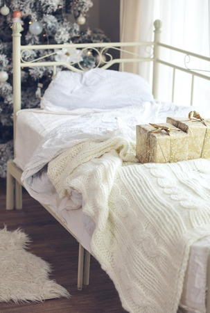 christmas morning: Wrapped presents on a bed near decorated Christmas tree in hotel room in the morning Stock Photo