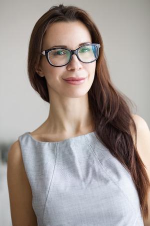 30 세 젊은 여자 실내에 서서 카메라를 찾고 안경을 착용