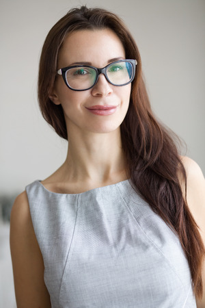 girl glasses: 30 years old young woman wearing glasses standing indoors and looking at camera Stock Photo