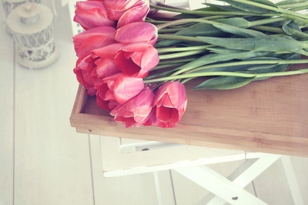 shabby: Vintage shabby chic photo of bouquet of spring tulips on a wooden tray on white wooden floor