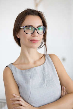 30 years old young woman wearing glasses standing indoors and looking at camera Stock Photo