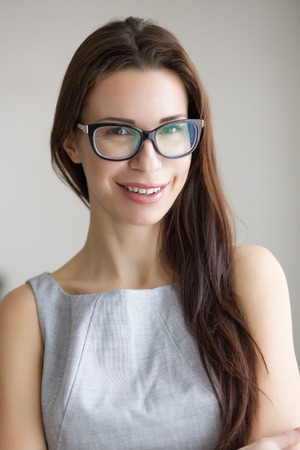 30 years old: 30 years old young woman wearing glasses standing indoors and looking at camera Stock Photo