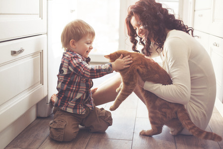 smiling cat: Mother with her baby playing with pet on the floor at the kitchen at home Stock Photo