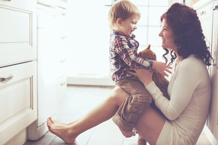 Mother with her baby playing with pet on the floor at the kitchen at home Banque d'images