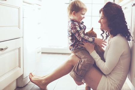 Moeder met haar baby spelen met een huisdier op de vloer in de keuken thuis