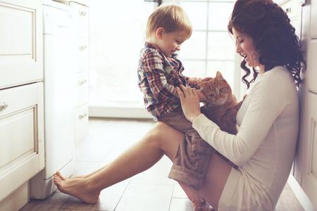 personas felices: Madre con su beb� que juega con mascotas en el piso en la cocina en el hogar