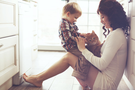 Mother with her baby playing with pet on the floor at the kitchen at home Stock Photo