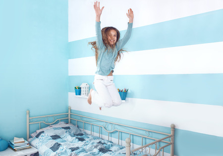 blue room: 8 years old kid girl jumping on the bed at her room