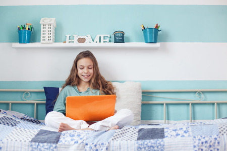 8 years old: 8 years old child having fun using laptop at her bedroom Stock Photo