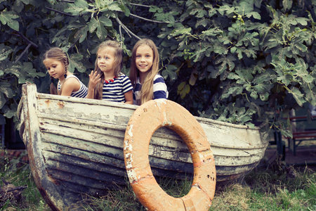 Kids playing inside old boat in summer